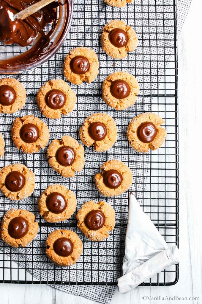 Peanut Butter Kisses on a cooling rack with ganache filled centers.