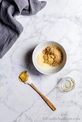 Mixing breadcrumbs and dijon mustard in a bowl.