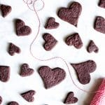 Vegan Dark Chocolate Shortbread Cookies on a marble counter, cut into heart shapes.