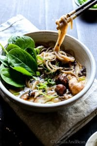 Speedy Miso Spinach Mushroom Ramen in a bowl with chop sticks picking up noodles.