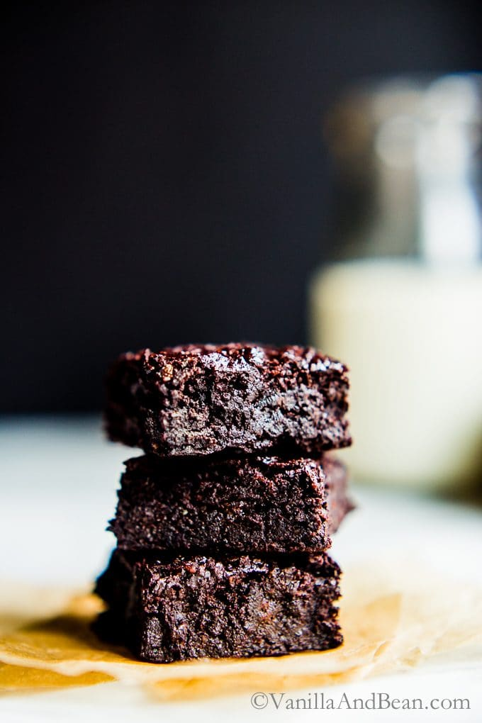 Chocolate Hazelnut Brownies stacked up with milk in the background.