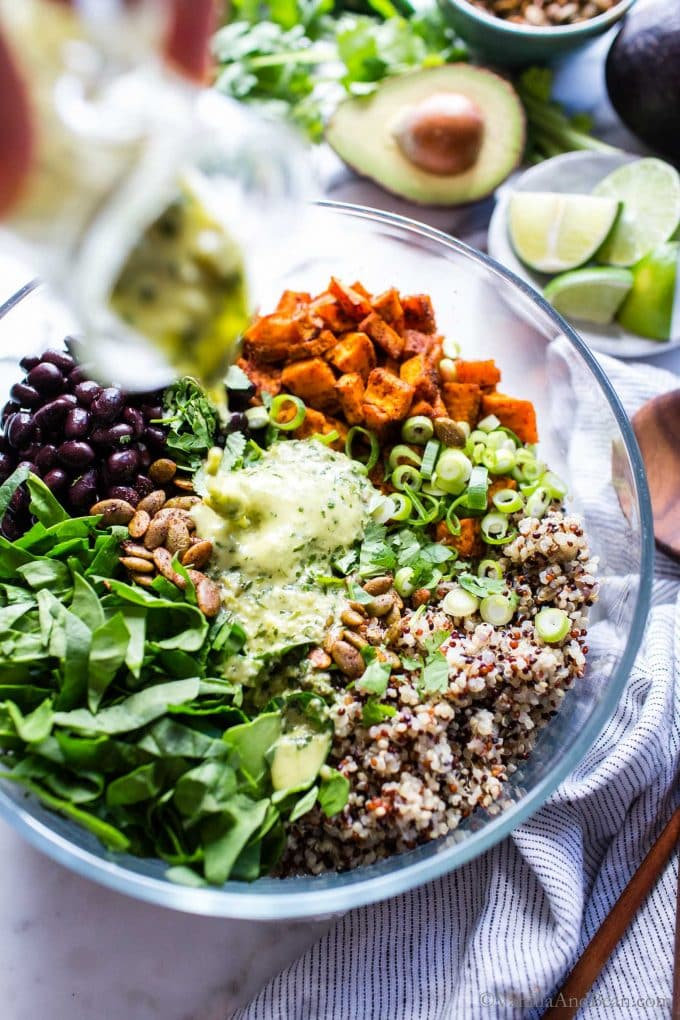 Sweet Potato Quinoa bowl with black beans with dressing poured over the top