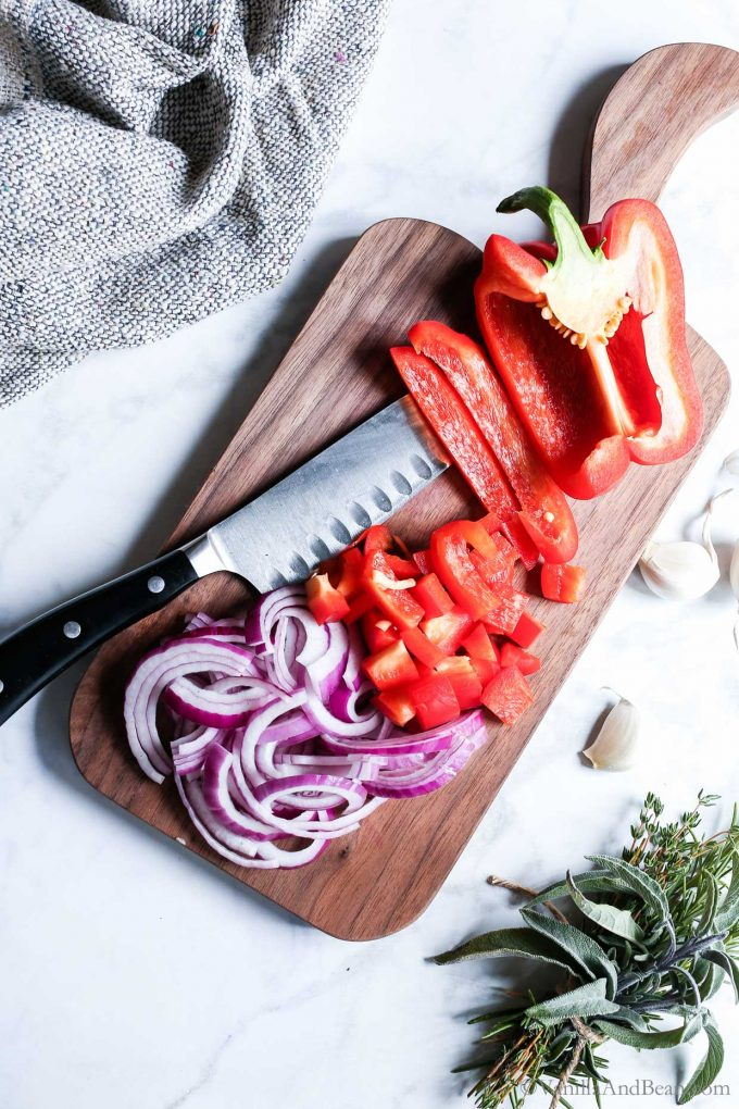 Chopped onions and bell pepper on a cutting board.