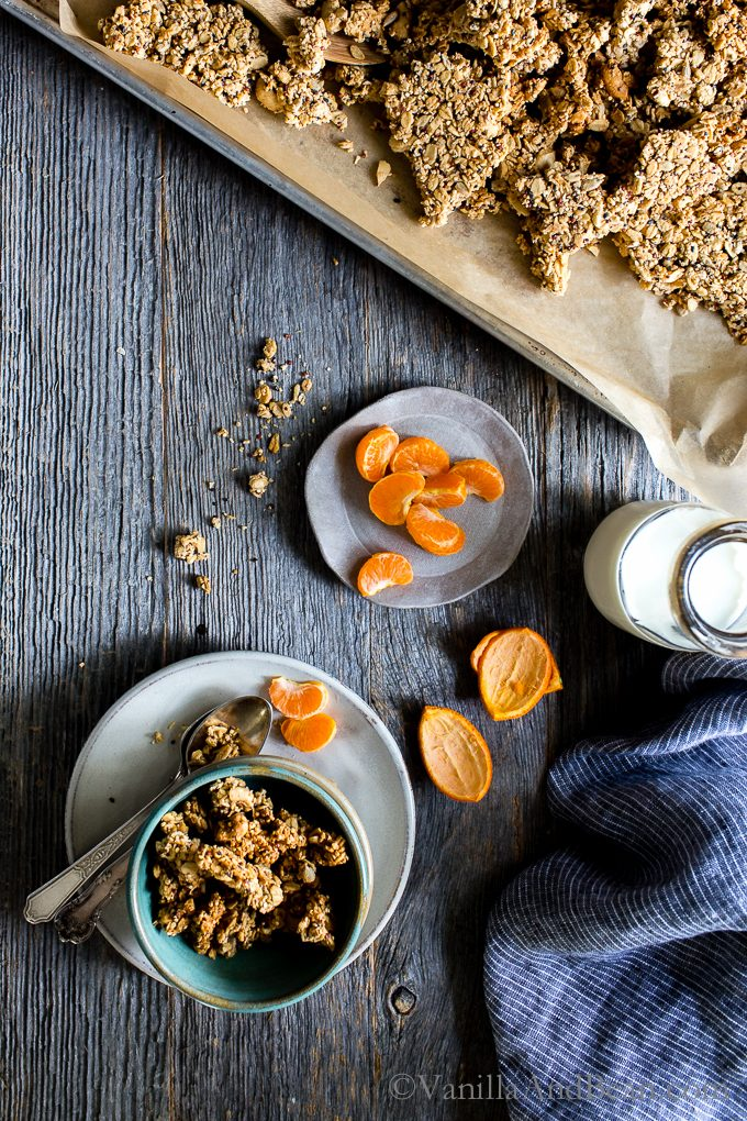 Lemon Tahini Cashew Granola in a pan with a bowl full and orange wedges on the side.
