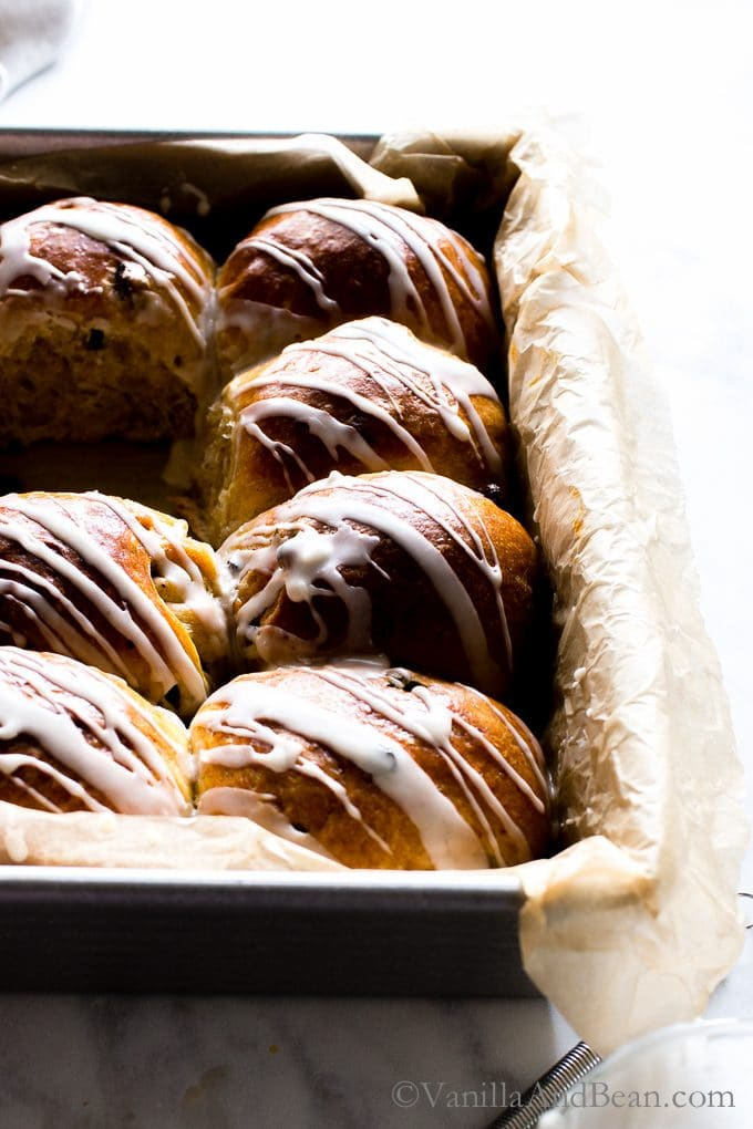 Hot Cross Buns with Rum Soaked Currants in a pan drizzled with glaze.