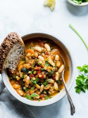 Overhead shot of smoky white bean stew with a slice of bread and spoon in the bowl.