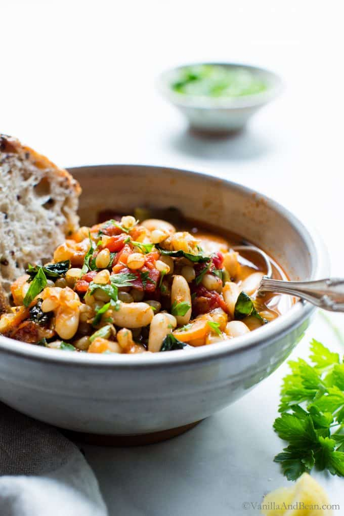 Wheat Berry Stew in a bowl with a spoon and a slice of bread.