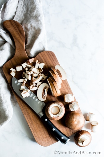 Slicing mushrooms on a cutting board.