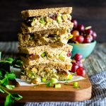 Smashed Chickpea Salad with Pecans and Grapes tea sandwiches stacked up on a cutting board.