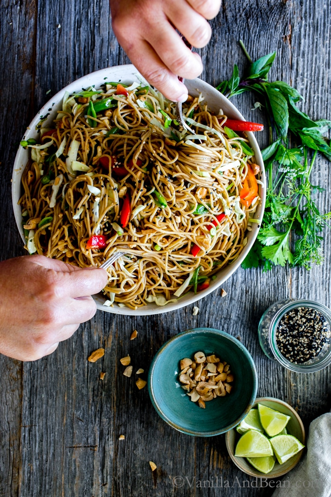 Sesame-Ginger Noodle Salad with Cashews in a big serving bowl being tossed with a side of sesame seeds, cashews and lime.