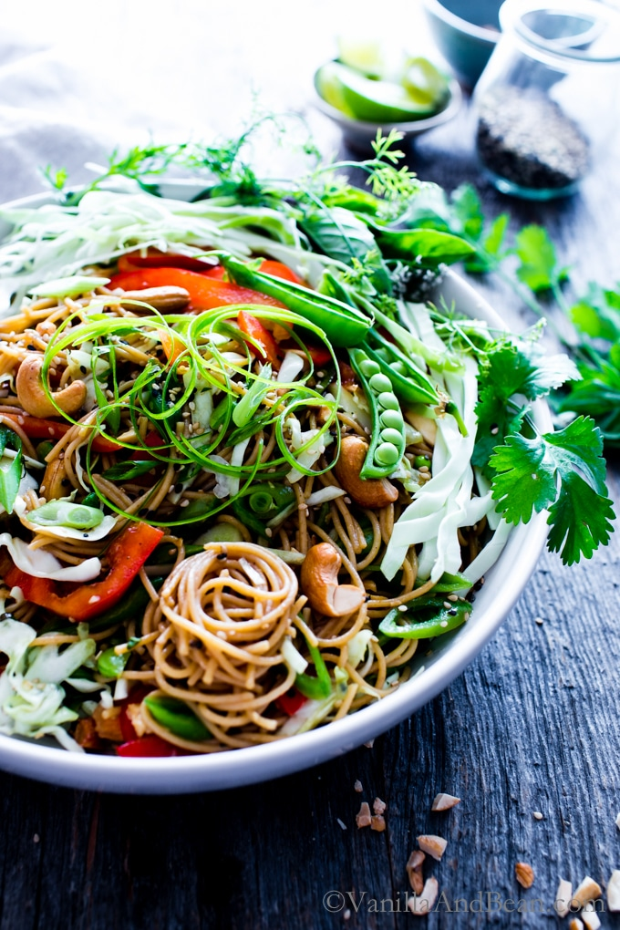 Sesame-Ginger Noodle Salad with Cashews in a big serving bowl with a side of sesame seeds, cashews and lime.