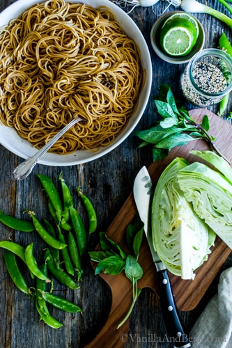 A big bowl of sesame noodles surrounded by crunchy veggies like cabbage, herbs and snap peas.