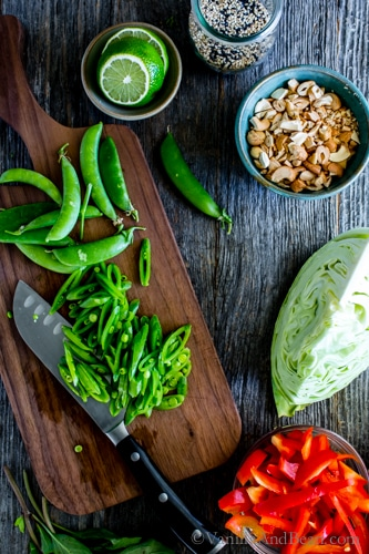 Slicing snap peas on a cutting board surrounded by red bell peppers, cabbage, limes and cashews.