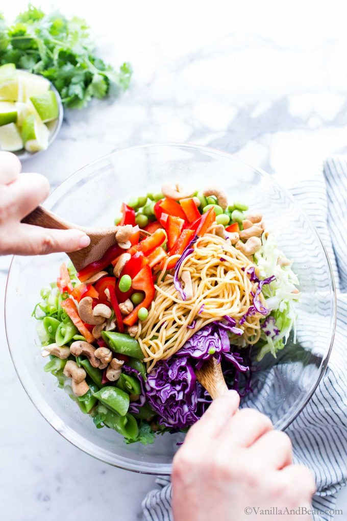Tossing the Asian Noodle Salad in a big bowl.