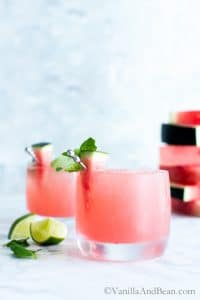 Watermelon Mojitos in ice filled glasses garnished with a watermelon wedge.