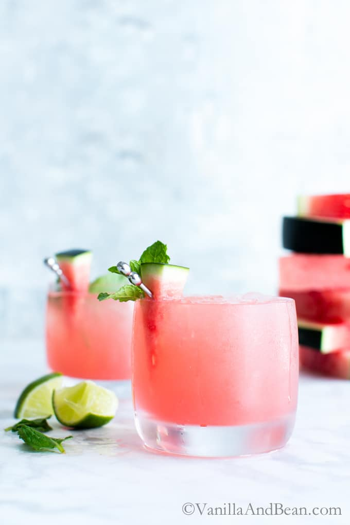 Watermelon Mojitos garnished with watermelon and a mint sprig.