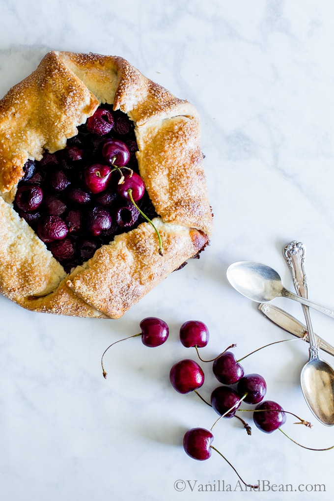 Sweet Cherry Galette topped with several spoons on the side ready to dig in.