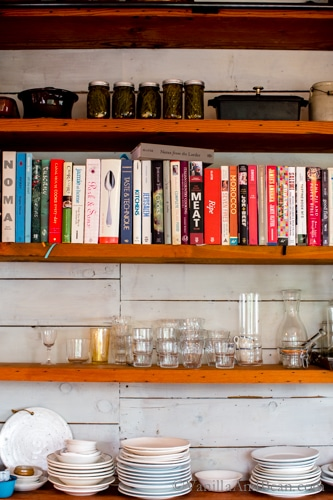Recipe books, dishes and glasses setting on kitchen shelves.