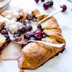 Sweet Cherry Galette topped with ice cream and several spoons digging in.