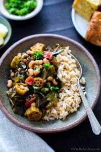 Harissa Stewed Black-Eyed Peas with Okra and Collard Greens in a bowl with brown rice ready for sharing.
