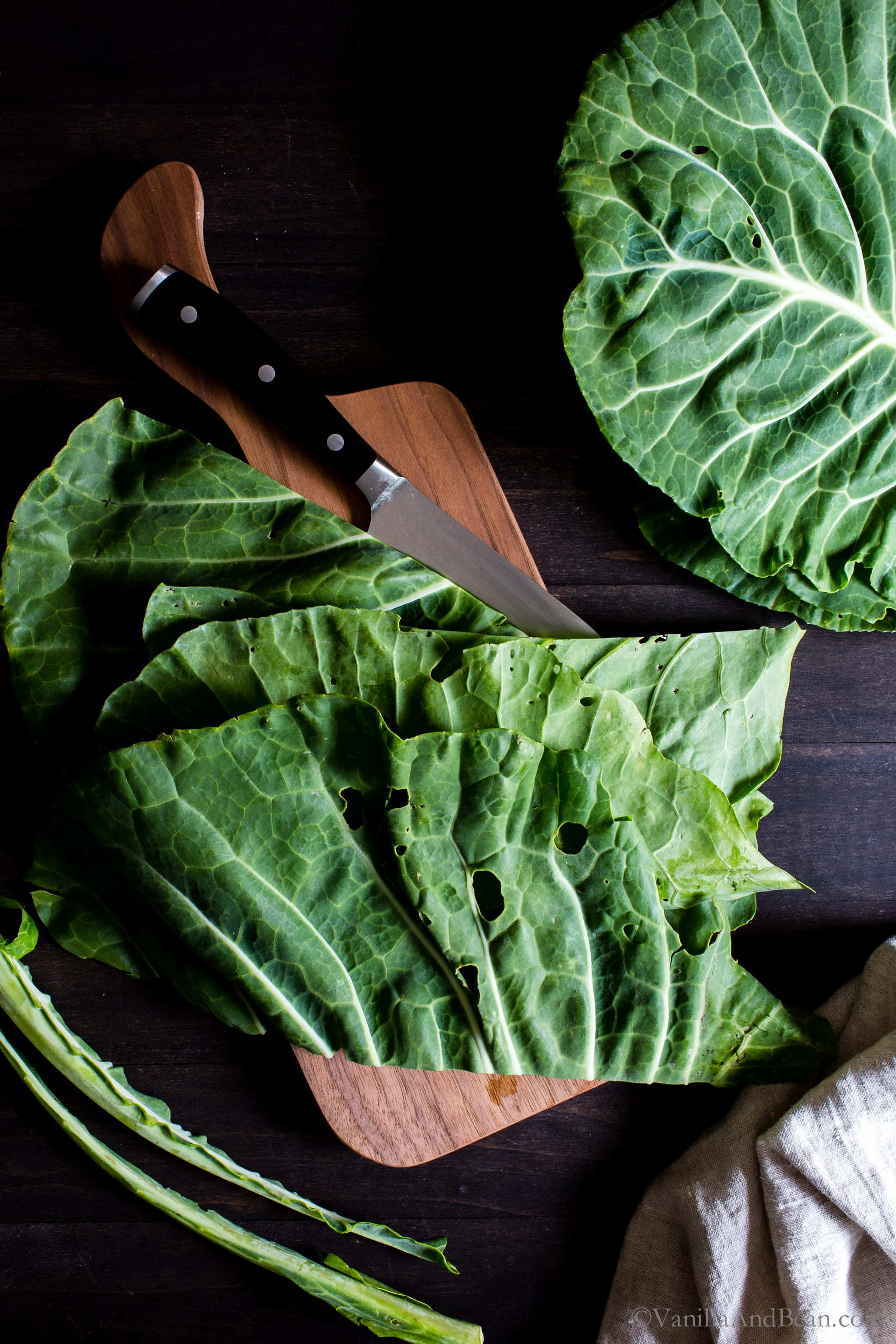 Chopping collard greens on a cutting board.