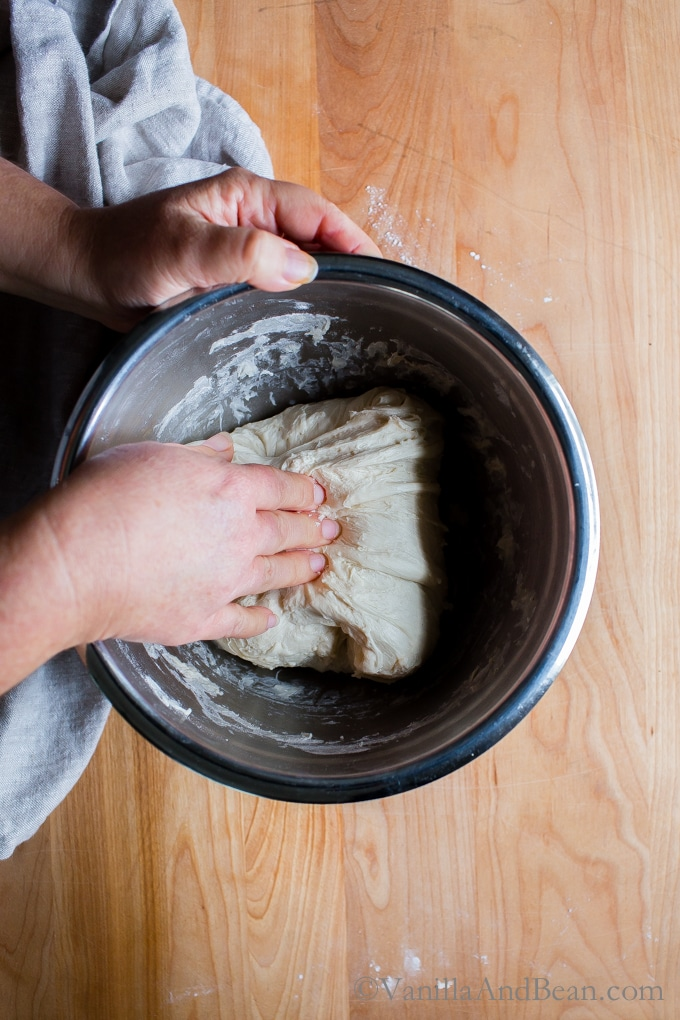 Woman's hand folding sourdough in a bowl.