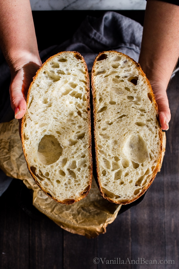 Woman's hands with cut open sourdough bread.