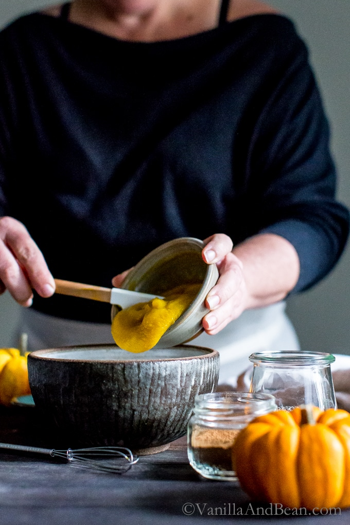 Adding pumpkin puree to a bowl.