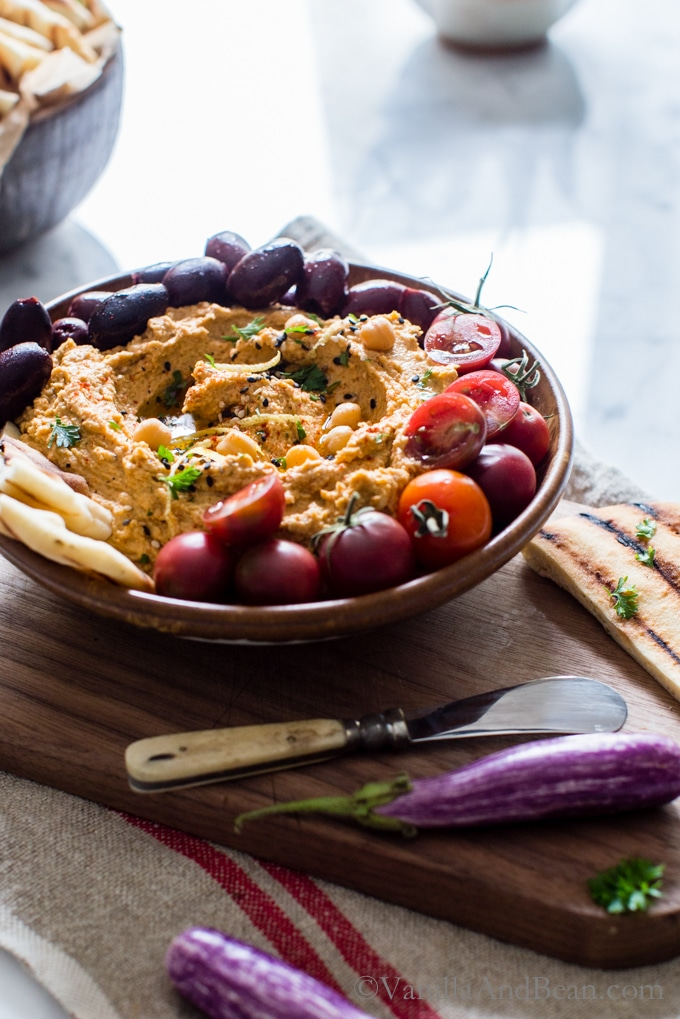 Roasted eggplant hummus on a cutting board shared with Naan, olives and tomatoes.