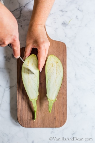 Scoring the flesh of the eggplant on a cutting board.
