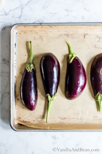 Eggplants, flesh side down on a parchment lined sheetpan.