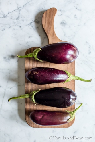 Four eggplants lined up on a cutting board.