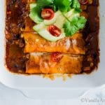 Sweet Potato Wrapped Black Bean Enchiladas in a casserole dish topped with avocado and cilantro ready for sharing.