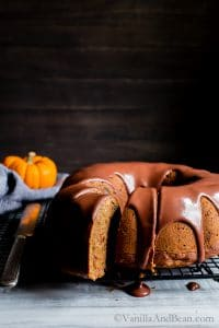 Pumpkin Pecan Bundt Cake with Chocolate Maple Drizzle with one slice just cut and ready for sharing.