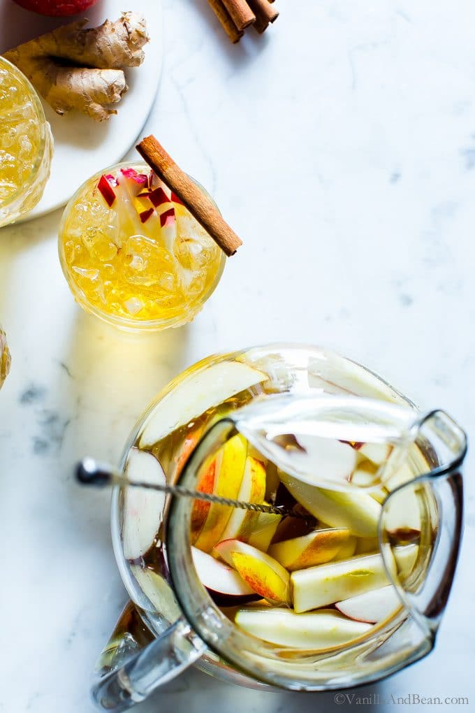 Overhead shot of Sparkling Apple Bourbon Sangria garnished with apples and a cinnamon stick.