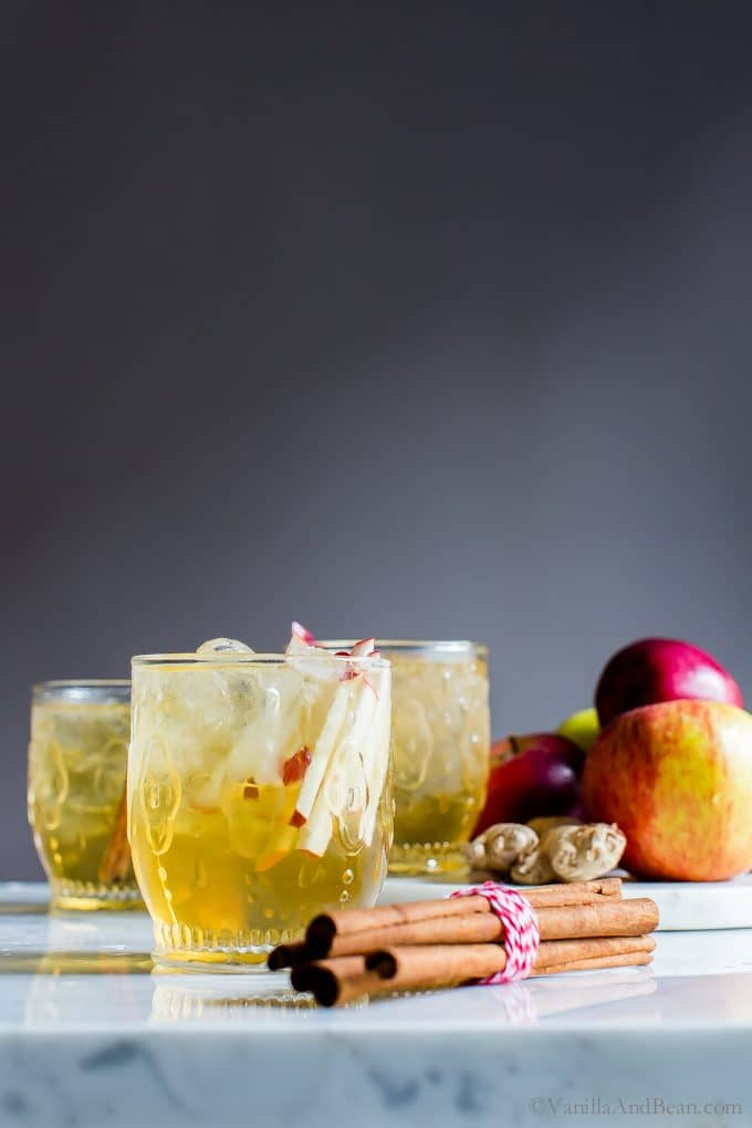 Sparkling Apple Bourbon Sangria in ice filled cocktail glasses, garnished with fresh apple slices and cinnamon sticks.