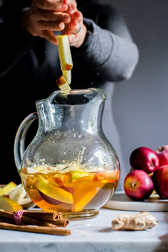 Adding sliced apples to a pitcher filled with white sangria.