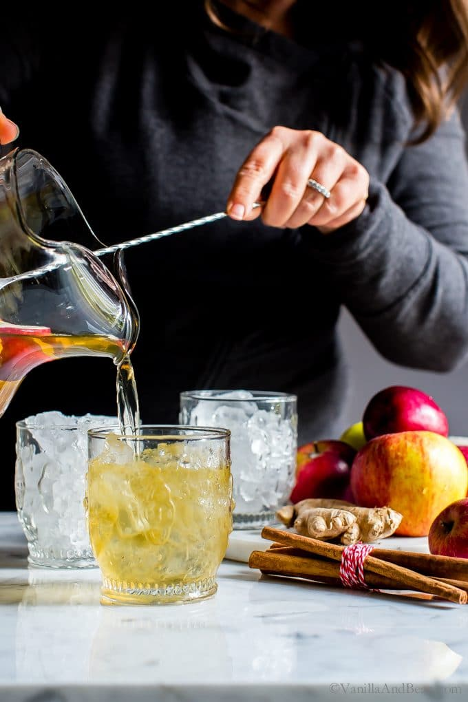 Pouring Sparkling Apple Bourbon Sangria into ice filled cocktail glasses.