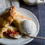 Tender pastry wrapped around half an apple stuffed with a mix of brown sugar, cinnamon, butter and cranberries on a plate with a scoop of ice cream.