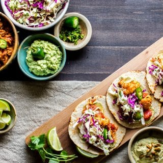 A weeknight staple,Roasted Cauliflower Tinga Tacos with Chili-Lime Slaw are chipotle spicy, and packed with flavor. They're freezer friendly and done in about 30 minutes! Serve with your favorite Mexican inspired sides and don't forget the guacamole! #vegan + optionally #glutenfree #Tacos #recipe #Vegetarian