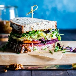 Flavor and texture rich, simple ingredients shine in this Roasted Beet and Sauerkraut Sandwich with a good schmear of whole grain mustard to bring the flavors together. #veganRecipes #HealthyRecipes #VegetarianRecipes #RoastedBeets