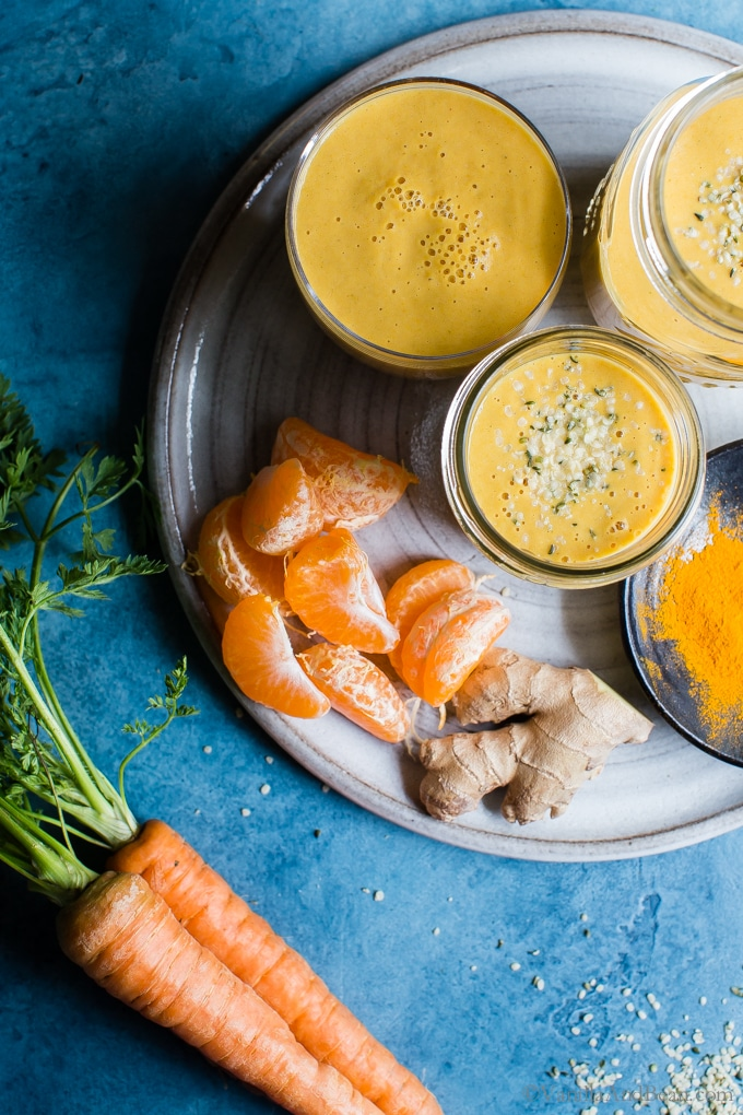 Overhead shot of Carrot-Ginger Citrus Immune Boosting Smoothie in three glasses on a plate ready for sharing.