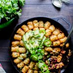 Vegetarian Chili Tater Tot Hotdish in a skillet with avocado and jalapeños on top, ready for sharing!