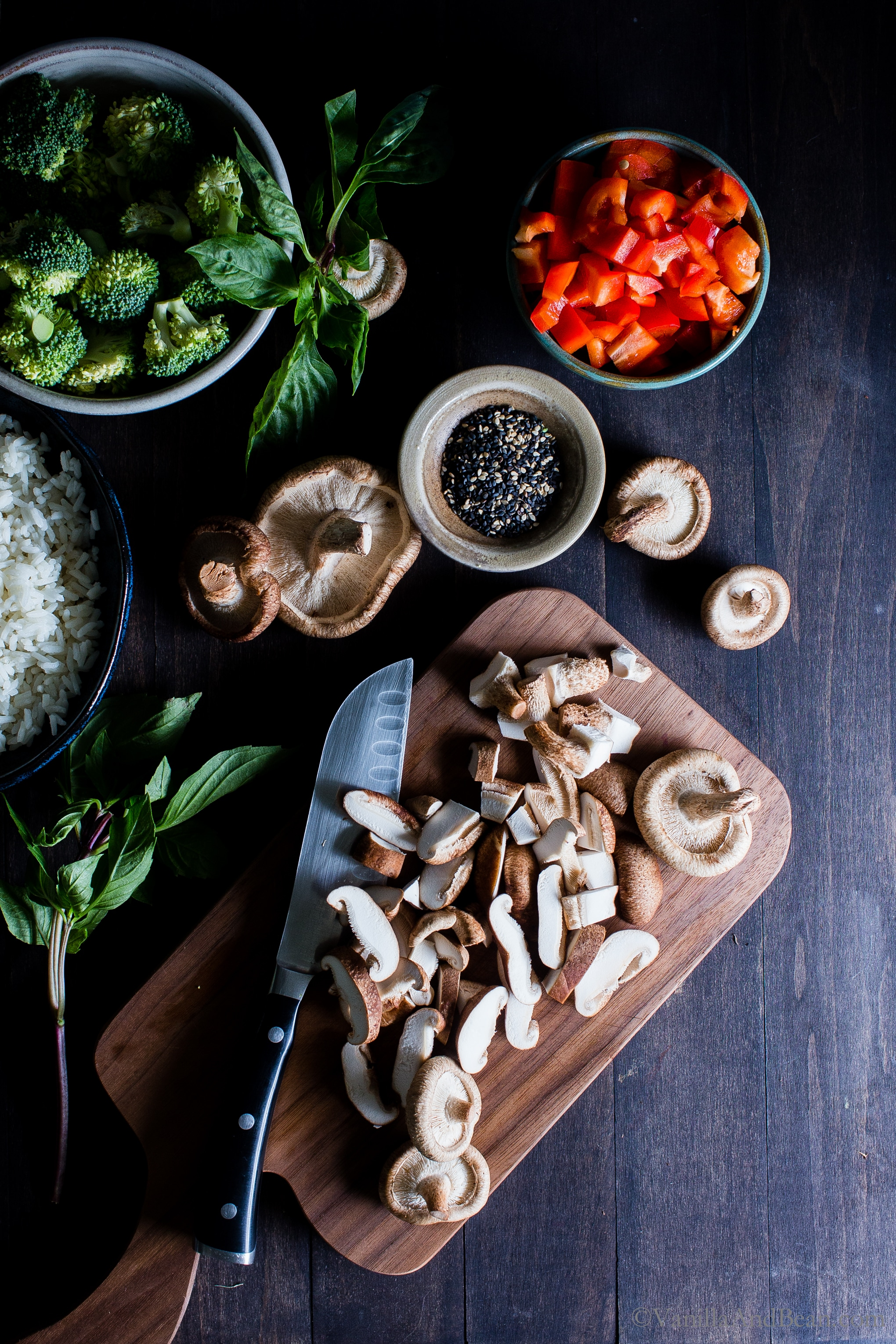 Ingredients for veggie fried rice with a focus on sliced mushrooms on a cutting board.