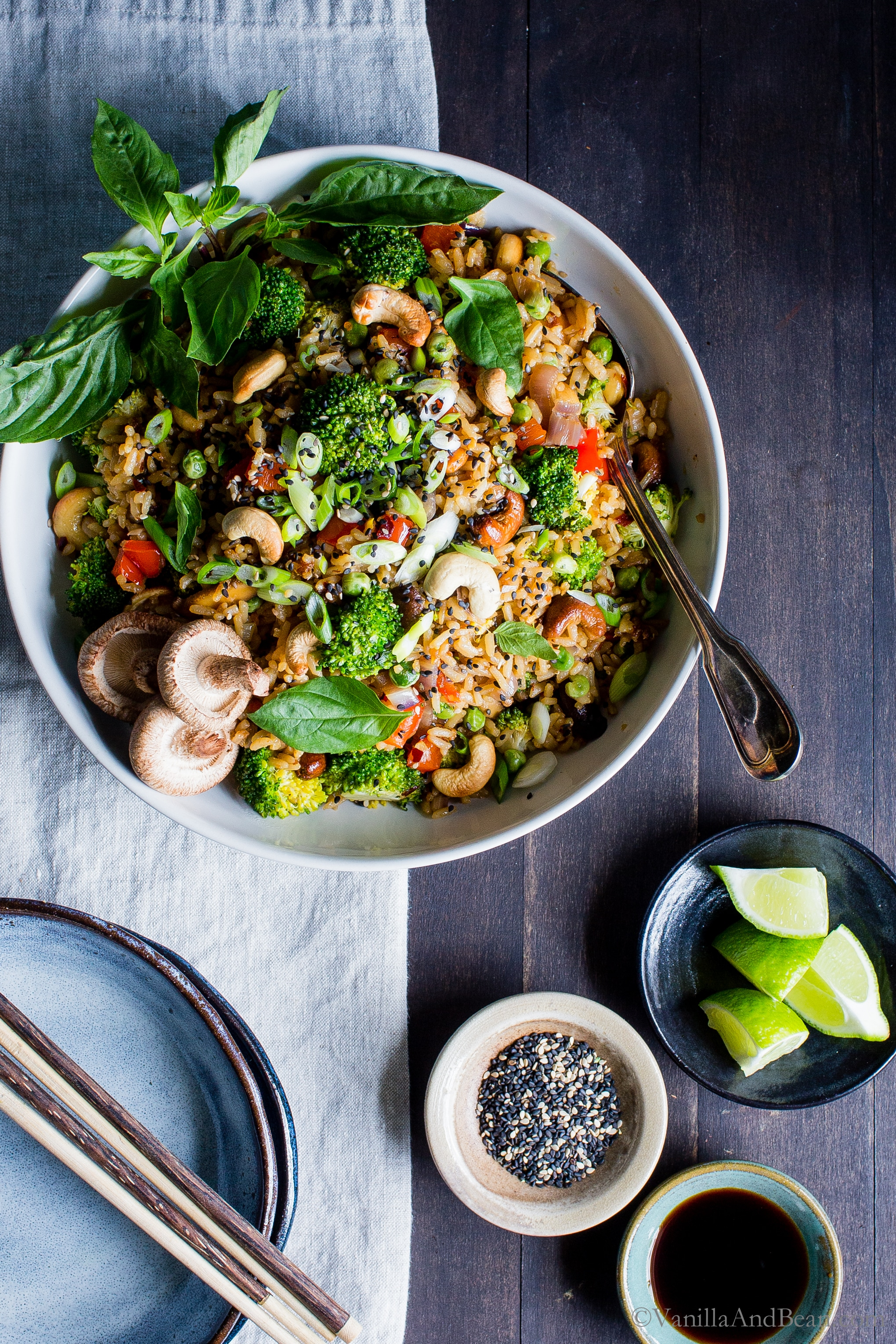 Overhead shot of Thai Vegetable Fried Rice with Cashews on a wood board with a linen cloth ready for sharing.