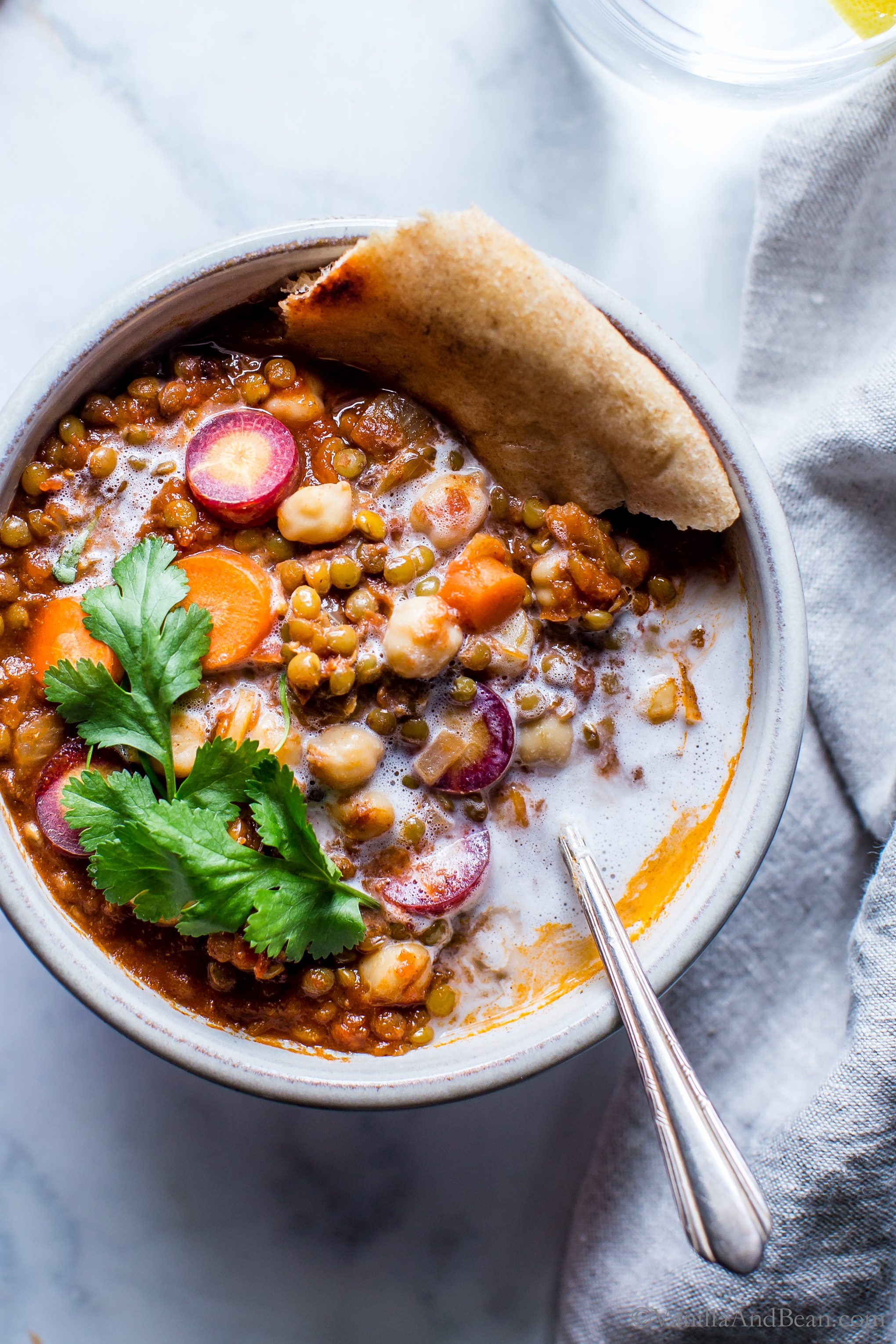 A bowl of Moroccan Lentil Chickpea Stew with pita bread, cilantro and a spoon.