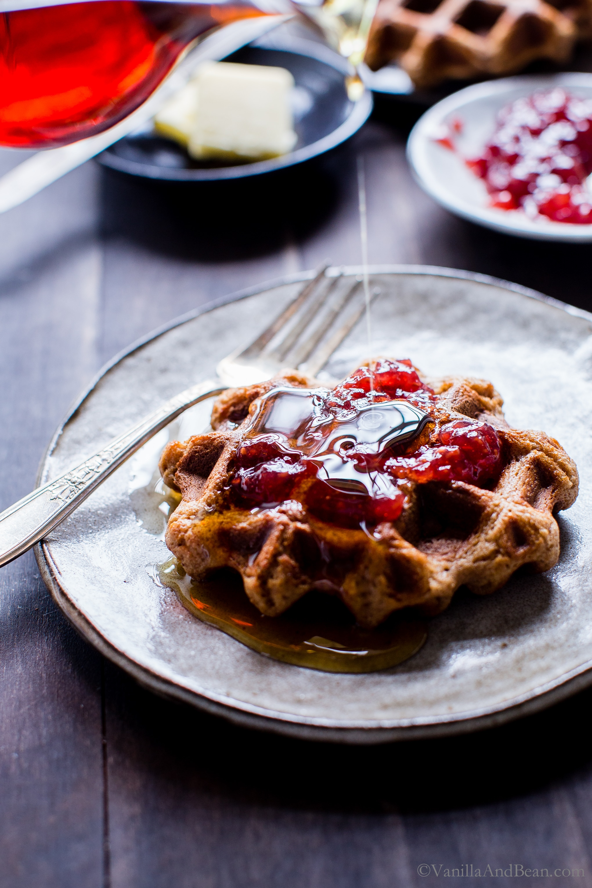 Banana-Pecan Oat Waffles on a plate with syrup drizzled over the top, ready for eating. .