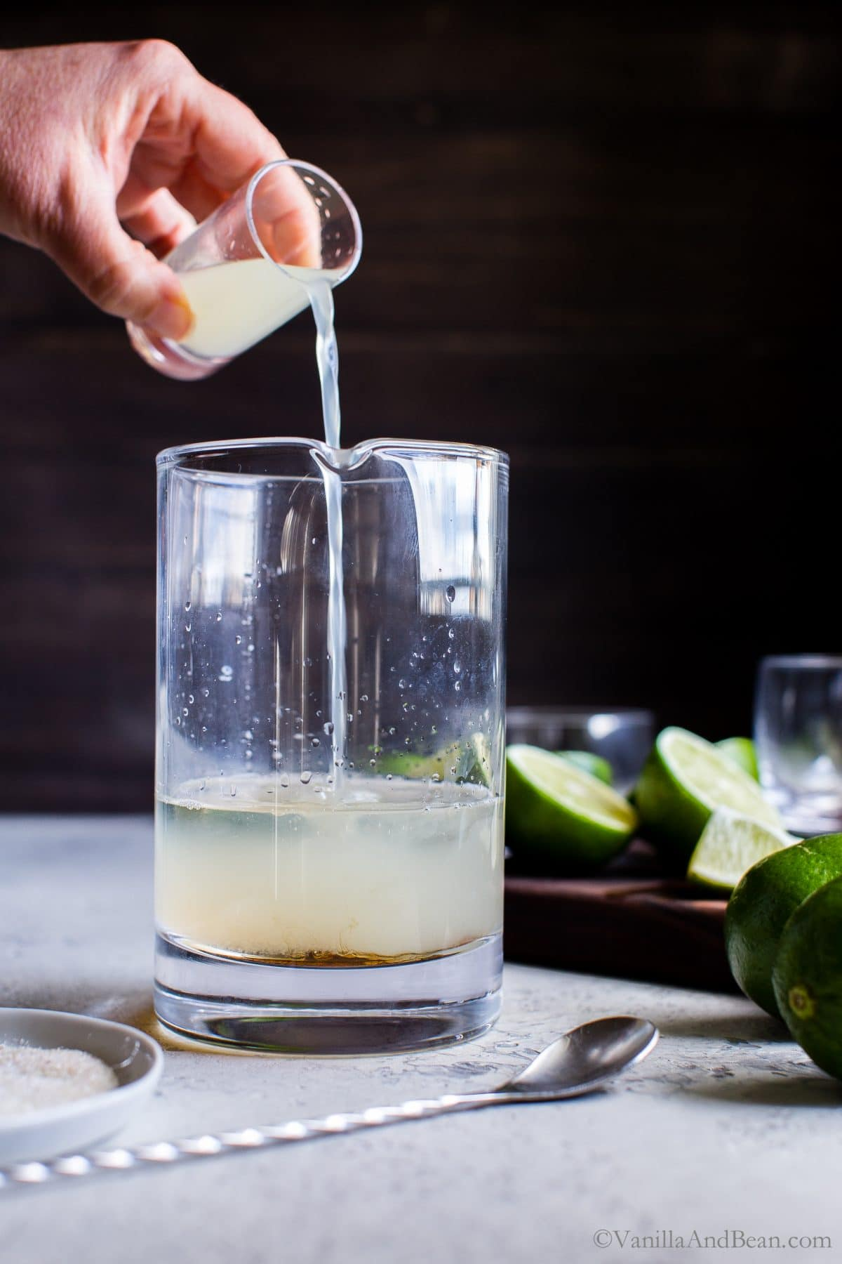 Pouring lime juice in a cocktail mixer for Mezcal Margarita Fizzes.