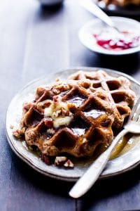 Banana-Pecan Oat Waffles drizzled with maple syrup on a plate ready for sharing.