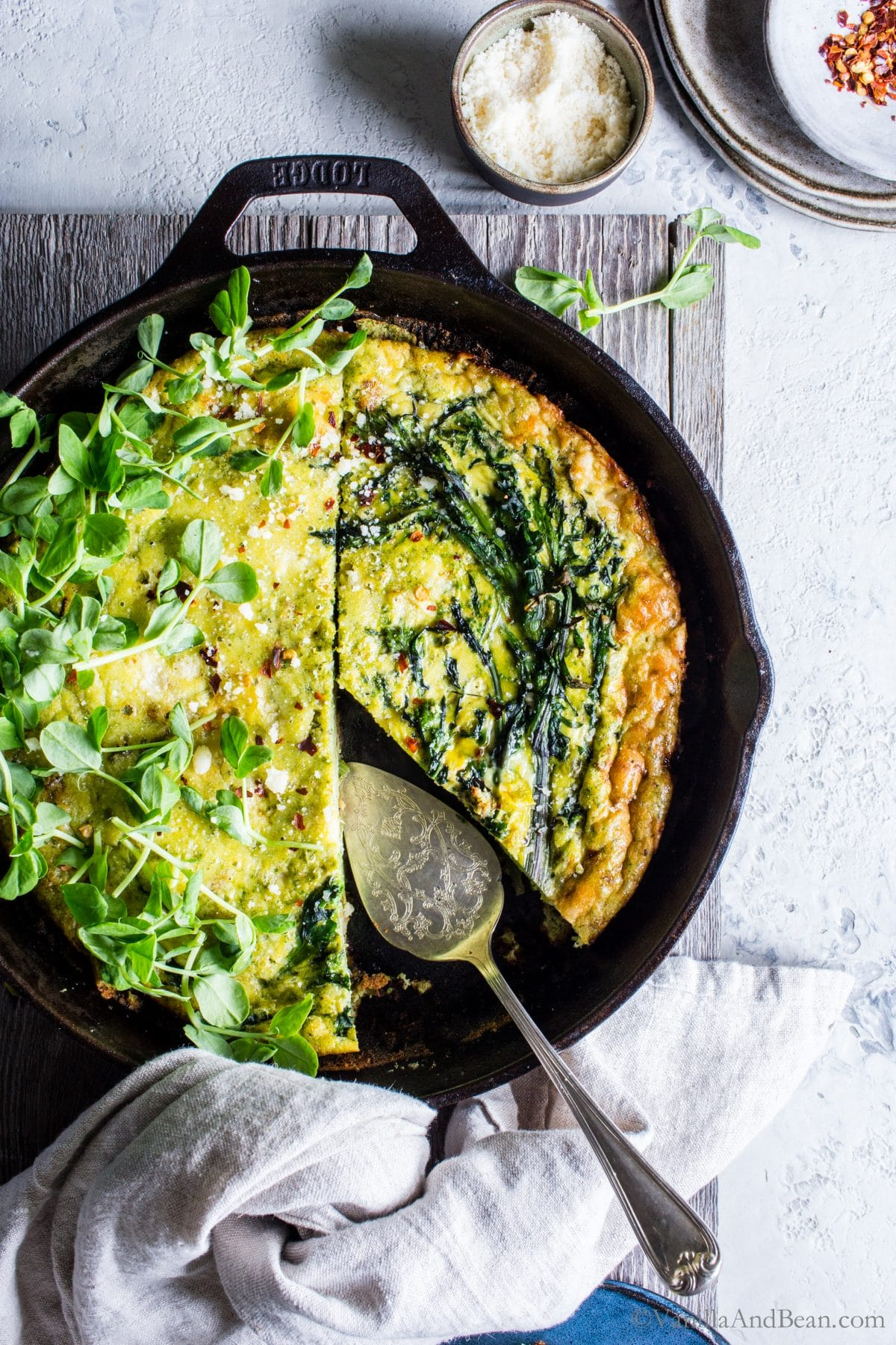 Overhead shot of Broccoli Rabe Frittata with Pesto Ricotta with a slice already shared from it.